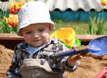 Playing child. Baby boy playing at the sandy playground Stock Image