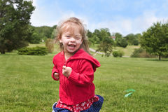 Playing Child. Toddler happily running through park Royalty Free Stock Image