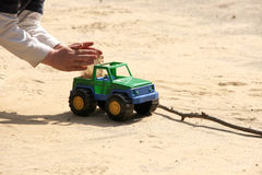 Playing child filling sand in a toy car Royalty Free Stock Photos