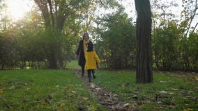 Playing with a child, a happy mother enjoys her motherhood and a charming female child having fun in autumn park on a