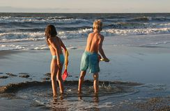 Playing children. Children at the beach in the late afternoon sun stock image
