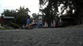 Playing children striking slippers running on asphalt street stock video