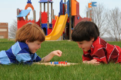 Playing Chinese Checkers. Two brothers play Chinese checkers in the park stock photo