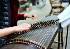 Playing the Chinese zither. A woman playing the guzheng. Guzheng is a traditional Chinese instrument, it belongs to the zither family of string Stock Photo