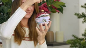 Playing with Christmas ball. Young pretty woman in red Christmas cap holding and twisting christmas ball in arm stock video footage