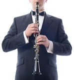 Playing the clarinet. Man in suit playing the clarinet isolated on white royalty free stock images