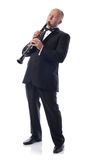 Playing the clarinet. Man in suit playing the clarinet  on white Royalty Free Stock Photography