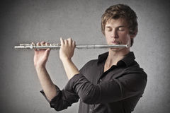 Playing the Clarinet. Blonde guy playing a clarinet royalty free stock photo