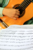 Playing classical guitar with music score Royalty Free Stock Photo