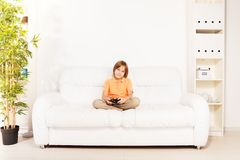 Playing Computer games. Happy smiling Caucasian boy gamer playing video games holding game controller sitting on the white sofa in living room Stock Photography