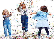 Playing with confetti. Little ecstatic girls playing with confetti Stock Photo