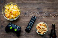 Playing console concept with chips on wooden background top view mock up. Playing console games concept with chips beer and joypad on wooden table background top Royalty Free Stock Photography