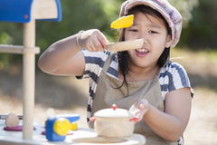 Playing cooking. Cute asian girls enjoy playing cooking Royalty Free Stock Photography