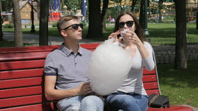 Playing With Cotton Candy. Cute couple in black sunglasses sitting on bench in park playing with cotton candy. Summer sunny day stock video footage