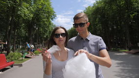 Playing With Cotton Candy. Man and woman in the park playing with cotton candy. Steadicam Shot. Summer sunny day stock video