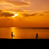 Playing Couple. Couple playing tennis at the beach during sunset Royalty Free Stock Images