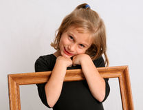 Playing coy. Young girl posing with empty picture fram Stock Photos
