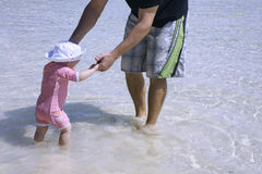 Playing with daddy. Baby daughter playing with daddy in the water Stock Photos