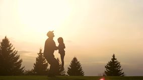 Playing with daughter in the evening park. Silhouette of military father lifting up and down little girl into the air stock footage