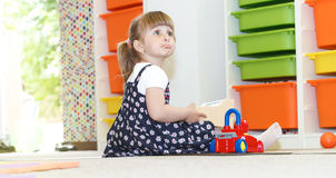 Playing at the daycare. Blonde little girl playing joyfull at the daycare stock photo