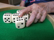Playing dice. Old woman hand playing with dice stock images
