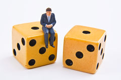 Playing Dice with Business. Miniature business man sitting on dice Royalty Free Stock Images
