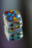Playing dice in transparent resin and multicolored numbers Stock Image