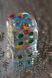 Playing dice in transparent resin and multicolored numbers Royalty Free Stock Photos