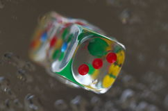 Playing dice in transparent resin and multicolored numbers Stock Photos