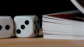 Playing dices and cards on a wooden table super close up macro on black background stock video footage