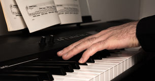 Playing a digital piano. Young man playing a digital piano, closeup Stock Photos