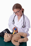 Playing doctor. Cute little blond girl dressed up like a doctor holding a pretend needle and a brown teddy bear smiling Royalty Free Stock Photo
