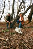 Playing with dog. Couple playing with their dog in a forest, by a nice autumn day royalty free stock photography
