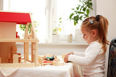 Playing with doll's house Stock Photography