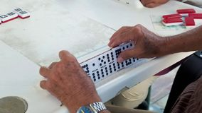 Playing domino game video. Slow motion high definition video of an elderly individual man playing the popular domino game stock video