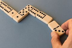 Playing dominoes on a blue background . Man`s hand with a Domino. Domino concept stock image