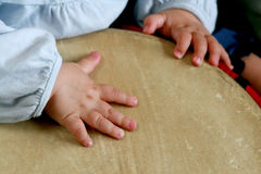 Playing the drum. Picture of 11 month olds hands drumming on an african djembe drum stock images
