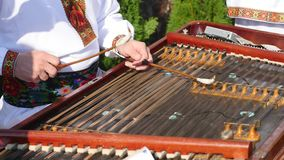 Playing the dulcimer folk musical instrument from Europe, playing the cymbals, cymbal, a young man playing cymbals stock video