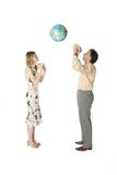 Playing with Earth. Man and woman playing with a big globe Stock Images