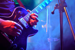 Playing Electric Guitar. Electric guitarist performing on stage Royalty Free Stock Photography