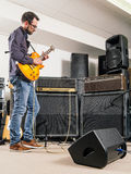 Playing electric guitar in a jam room Stock Image