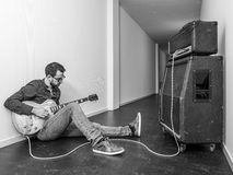 Playing an electric guitar in a long hallway Stock Images