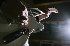 Playing electric guitar in studio closeup stock photography