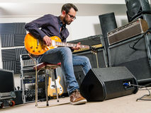 Playing electric guitar in a studio Royalty Free Stock Photo