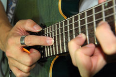 Playing electric guitar with tapping technic. Close up to the man playing electric guitar with tapping technic Stock Images