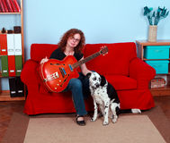 Playing electric guitar woman with dog Stock Photos