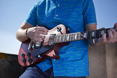 Playing electric guitar. Young man hands playing a les paul electric guitar on a roof terrace on a sunny day Royalty Free Stock Images