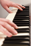 Playing An Electric Keyboard. Young man playing an electric keyboard. Left and  right hand shown Royalty Free Stock Photo
