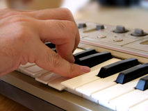 Playing electric synthesizer. Man's hand playing on electric synthesizer Stock Image