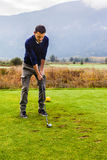 Playing on the fairway. A golf player making a swing on a vibrant beautiful golf course Royalty Free Stock Photo